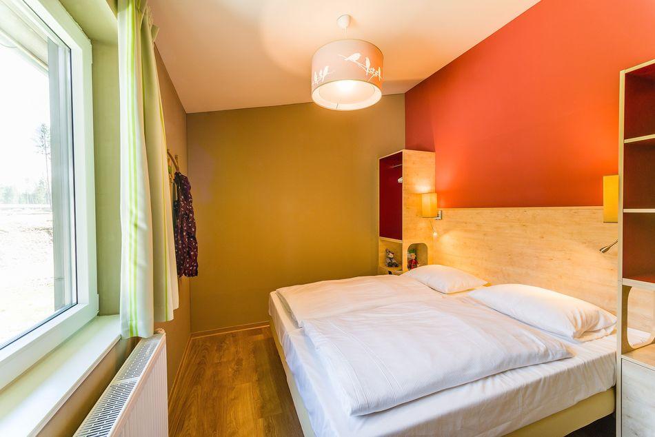 Die Rot- und Grüntone aus dem Wohnbereich finden sich im Schlafzimmer wieder.