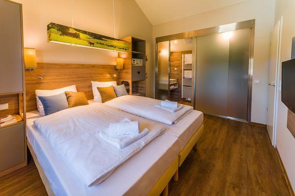 Eines der Schlafzimmer in den 6- und 8-Personen-Premium-Ferienhäusern besitzt ein En-Suite-Bad.