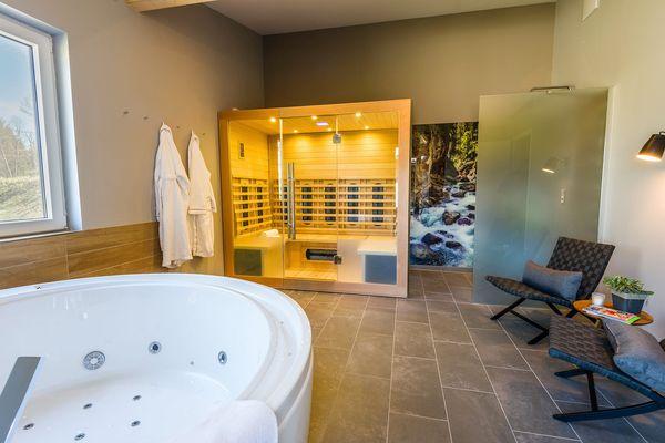Das großzügige Wellness-Badezimmer in den VIP-Ferienhäusern mit Sauna, Whirlpool und Regendusche.