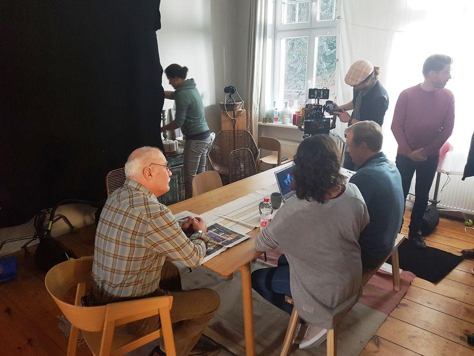 Schauspieler, Kameramann und Regisseur unmittelbar vor Drehbeginn am Esszimmertisch.