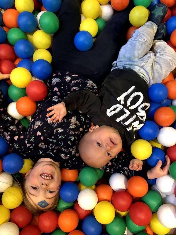 Die Kleinen stehen vor Freude Kopf in der Kinderspielwelt