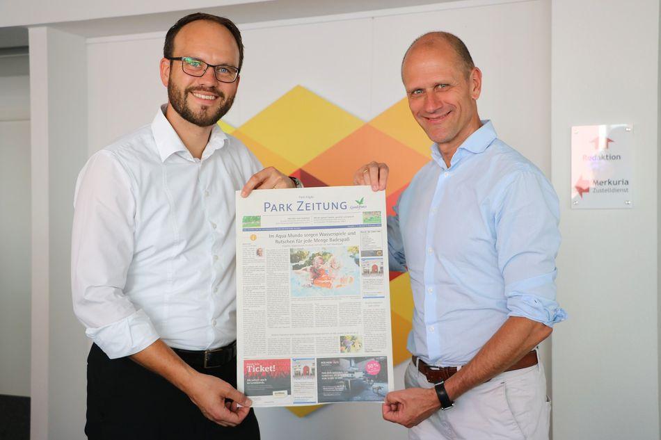 Tobias Pearman (links, Geschäftsführer Schwäbische Zeitung Leutkirch) und Christoph Muth (General Manager Center Parcs Park Allgäu) mit einem ersten Entwurf der Park Zeitung im Sommer 2018. Foto: Simon Nill