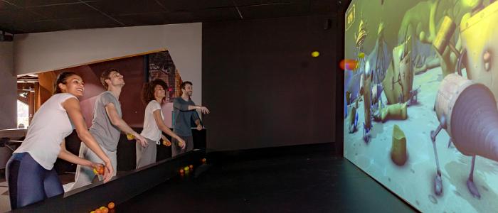 4 personnes envoient des balles en plastiques sur un écran