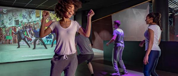 4 personnes dansent devant un écran en reproduisant les gestes projetés