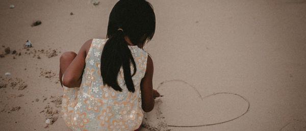Petite fille dessine sur le sable