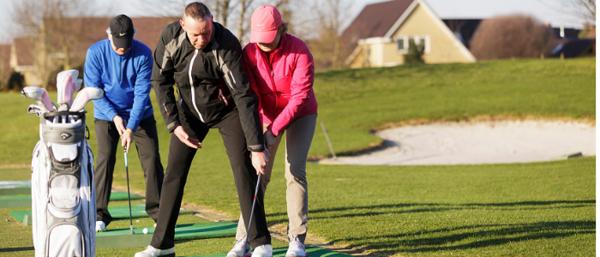 Au premier plan un homme âgé et une femme âgée s'entraîne au golf.