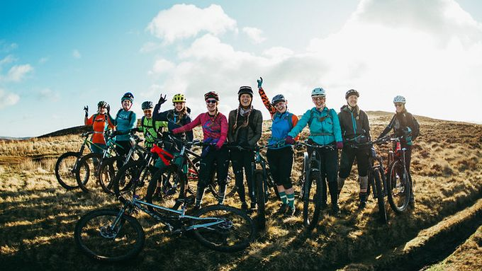 Group of a dozen women cyclists on a sunny hill smiling at camera