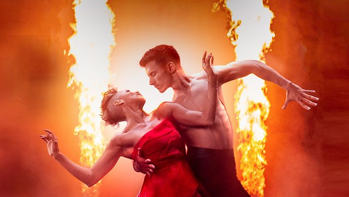 two dancers looking at each other with fire in the background
