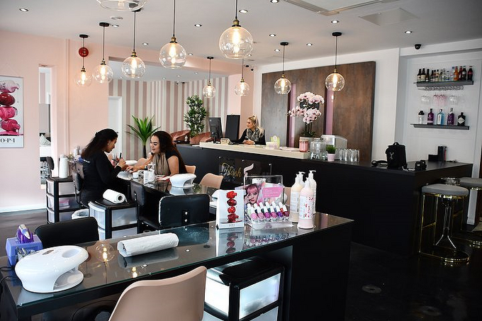 woman receiving nail treatment in a luxurious salon whilst receptionist types