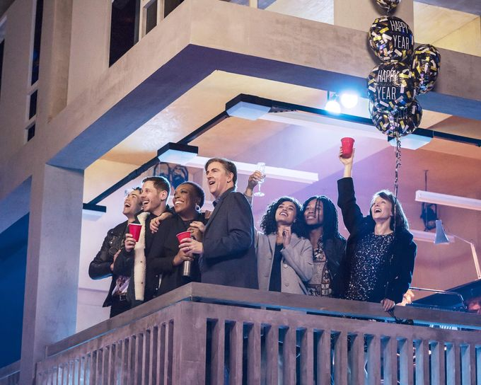 Group of people celebrating looking over balcony with balloons at night
