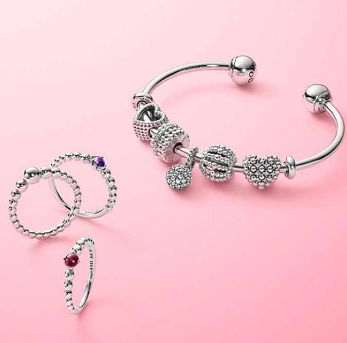 pandora bangle and stacker rings on a pink background