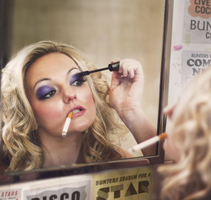Blonde woman applying mascara in mirror whilst smoking a cigarette