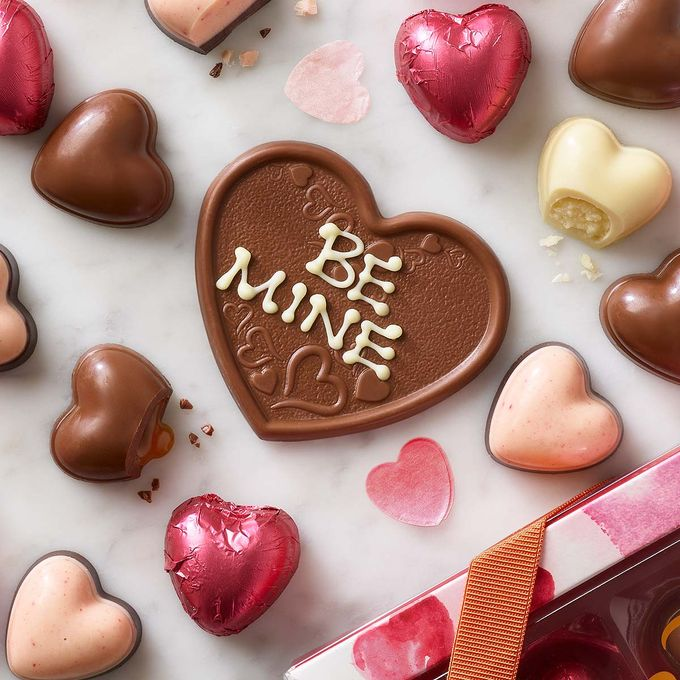 Chocolate heart with 'be mine' written with white icing, layed flat amongst smaller chocolate hearts