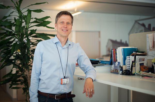 SATOn suunnittelupäällikkö Jussi Väisänen nojaa työpöytäänsä toimistossa.