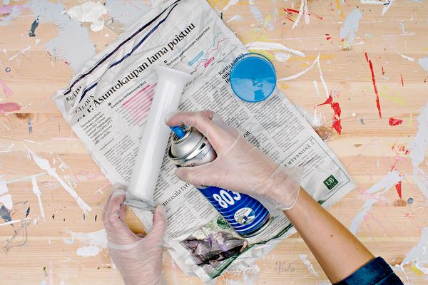 Kuvassa maalataan kynttilänjalkaa spraymaalilla. Alla sanomalehti ja kädessä hansikkaat.