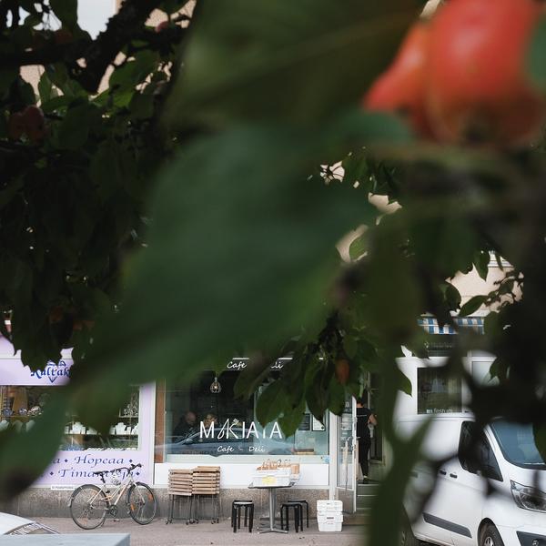 Omenapuiden siimeksestä näkyy Cafe Makiatan sisäänkäynti.