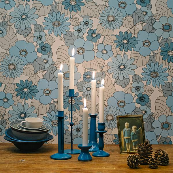 Kuvassa retroisa kukkatapetti ja asetelma kynttilänjalkoja tunnelmallisine kynttilöineen.
