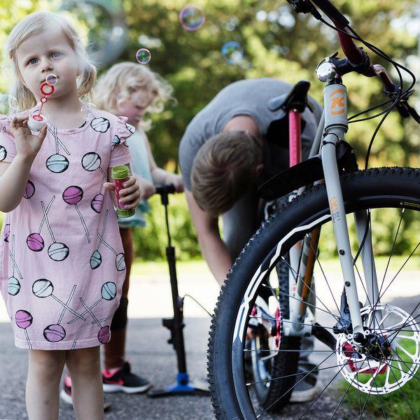 Josefiina puhaltelee ilmakuplia, kun isä ja sisko huoltavat pyörää