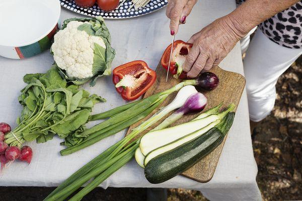Nainen leikkaa kasviksia ja vihanneksia pihalla