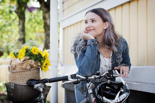 Kuvassa asukkaamme Ada kera polkupyörän, takakorissa keltaisia kukkia.