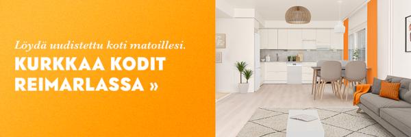 Kuvassa valoisa koti Reimarlassa. Etualalla on vaalea matto ja vaaleanharmaa sohva. Taustalla valkoinen keittiö.
