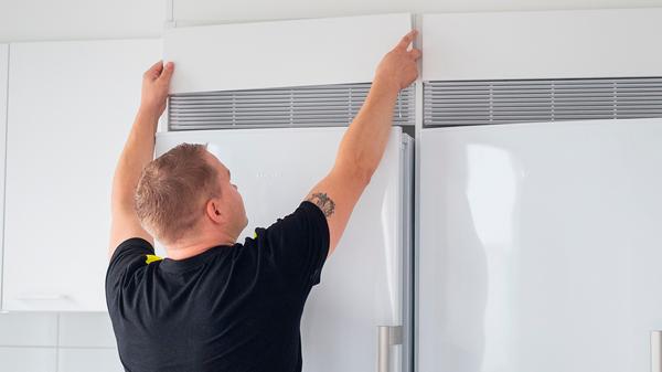 Eduard asentaa jääkaapin yläpuolelle suojakoteloa.