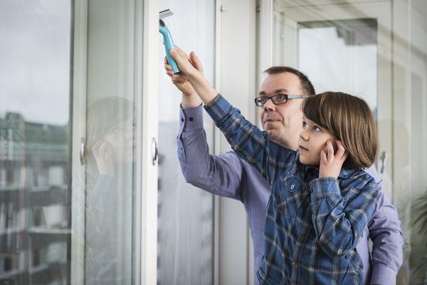 Isä ja poika pesevät yhdessä ikkunoita